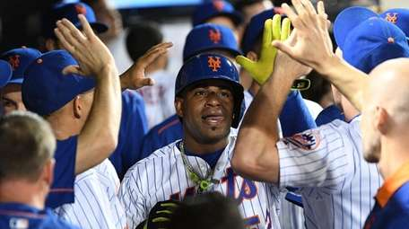 Yoenis Cespedes is greeted in the Mets' dugout