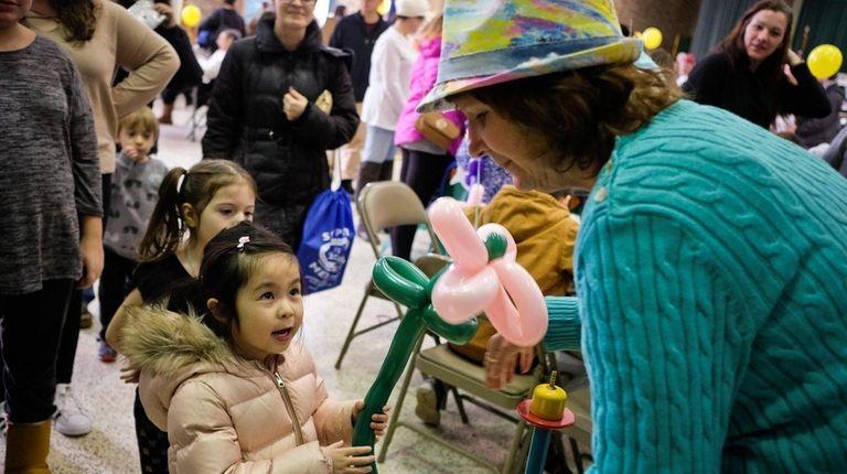 Graycen Louie, 4, of Queens, has a baloon