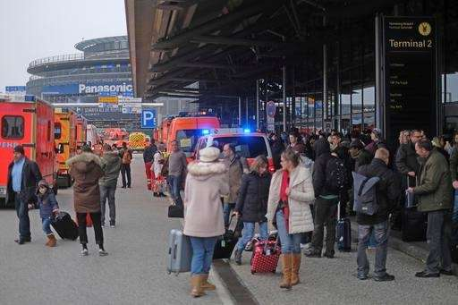 Travellers wait outside the Hamburg, northern Germany, airport