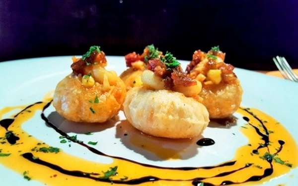 Indian pani puri (fried puffs) filled with Greek-style
