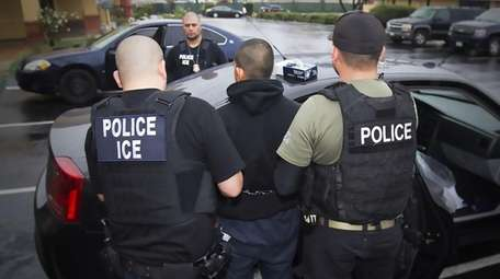 Immigration and Customs Enforcement officers detain a suspect