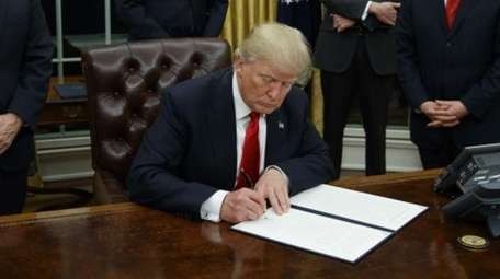 President Donald Trump signs his first executive order,