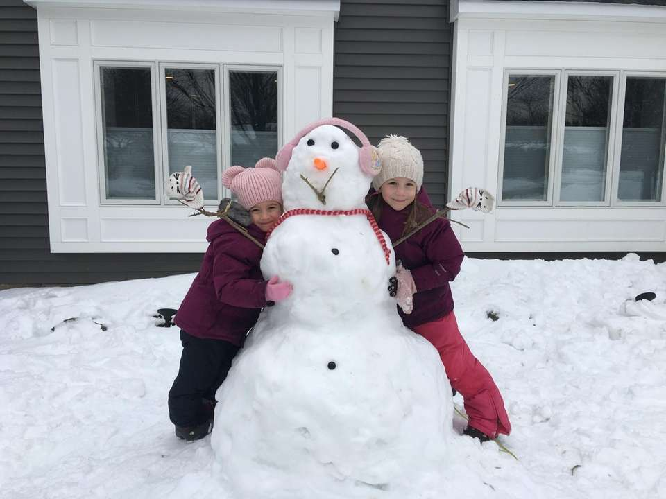 Reagan and Alex Dunn hugging their snowwoman in