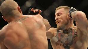 Conor McGregor, right, exchanges with Eddie Alvarez in the