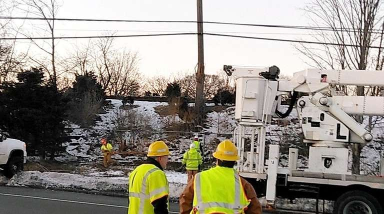 Workers tend to poles near the LIRR tracks