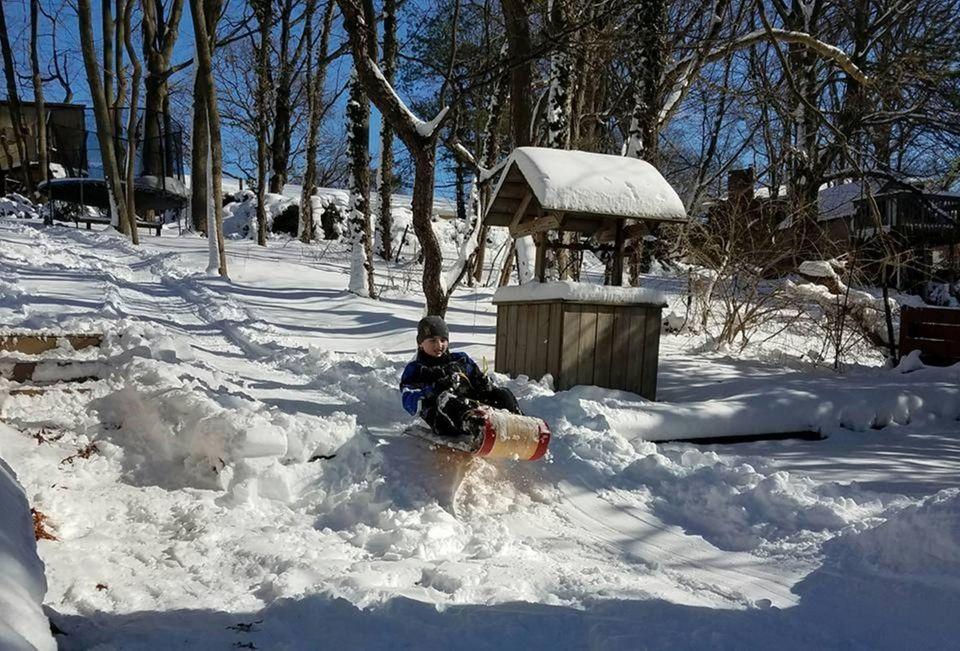 Jonathan age12 sleigh riding in his backyard