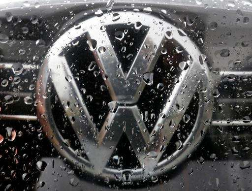 The Volkswagen logo is photographed through rain drops