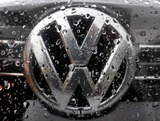 The Volkswagen logo is photographed through rain drops