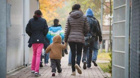 Refugees walk through a deportation center.