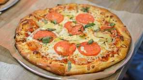 A custom-built pizza with tomatoes, mozzarella, artichoke hearts