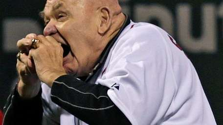 George Steele bites the baseball before throwing out