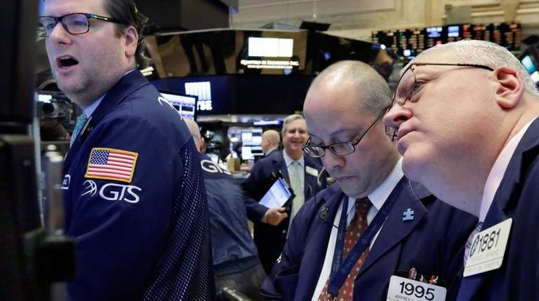 Specialist Gregg Maloney, left, works with traders Jeffrey