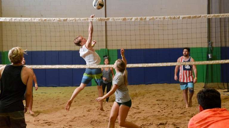 Katie Barto, center, moves to defend a spike
