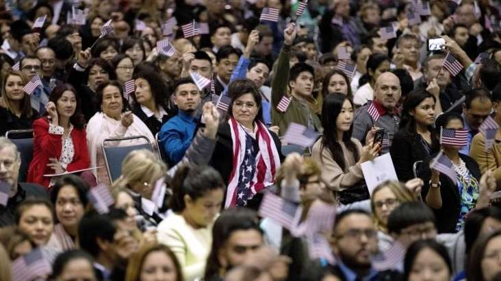 People wave U.S. flags during a naturalization ceremony