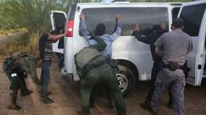 Detained immigrants are searched after being captured by