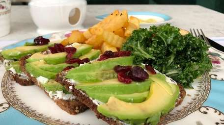 An open-faced sandwich of avocado and ricotta is