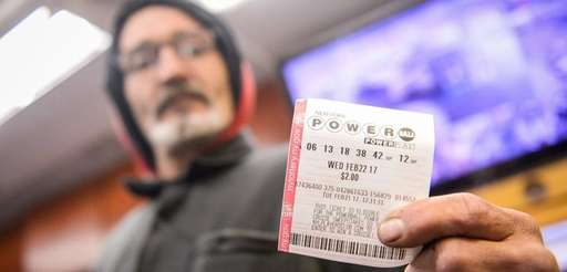 A customer holds a Powerball ticket at the