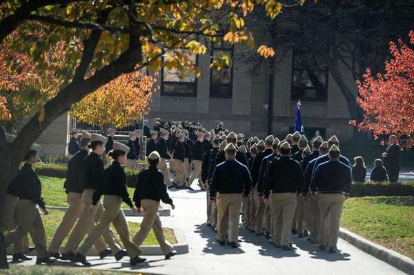 Midshipmen walk in file on the campus of