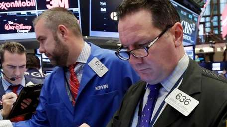 Traders, including Edward Curran, right, work on the
