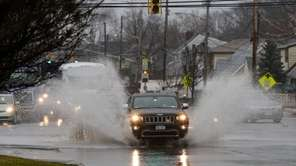 A car splashes through a puddle along the