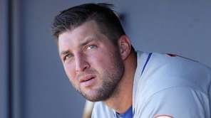 Tim Tebow watches from the dugout during an