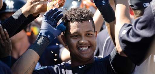 New York Yankees' Starlin Castro celebrates with teammates