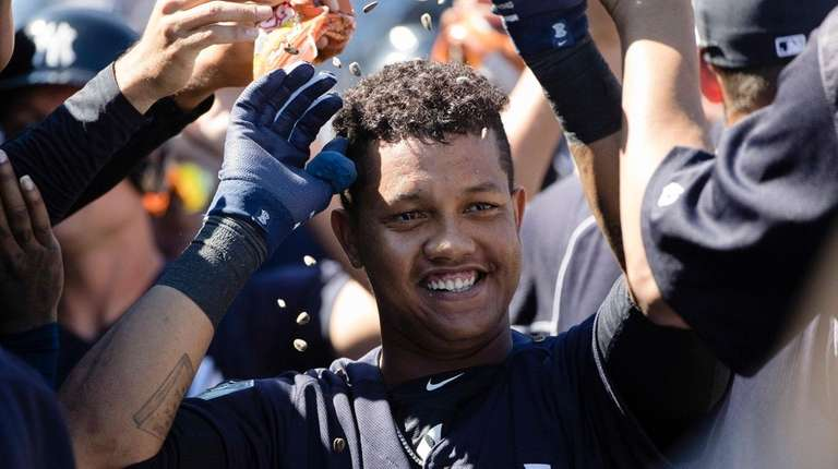 New York Yankees' Starlin Castro celebrates with teammates