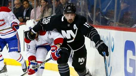 Cal Clutterbuck, #15, of the Islanders battles for