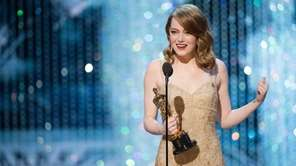 Actor Emma Stone, accepting the Oscar statuette she