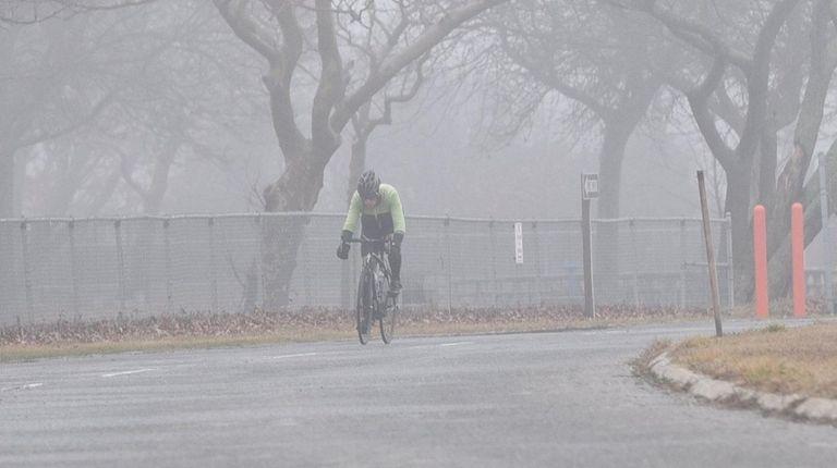 A man rides his bicycle at Heckscher State
