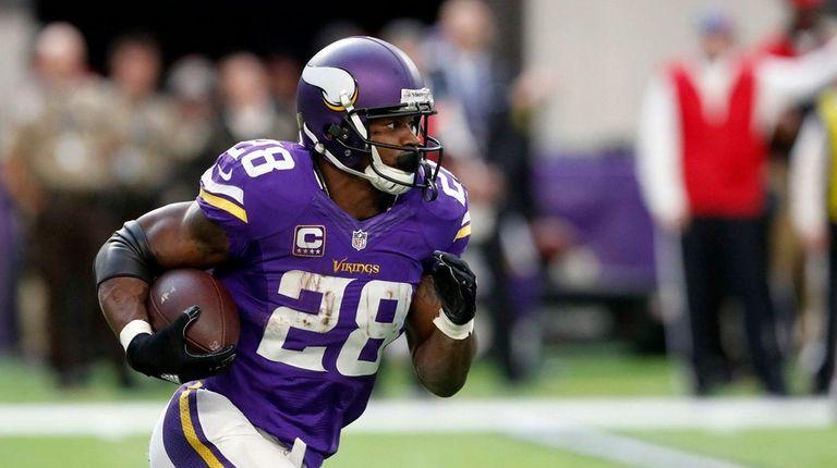 Minnesota Vikings running back Adrian Peterson runs with