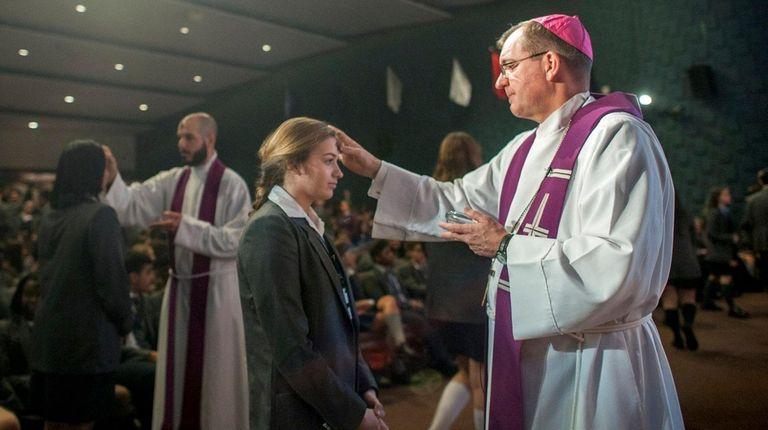 Bishop John Barres administers ashes at a Mass