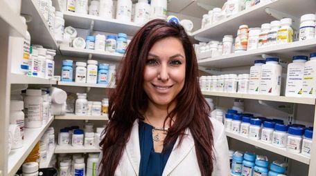 Pharmacist Saira Kahn stands inside Sun Ray Pharmacy