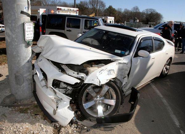 A sedan sits crumpled against a utility pole