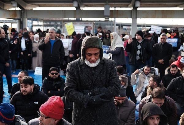 Muslim men pray at a prayer and demonstration