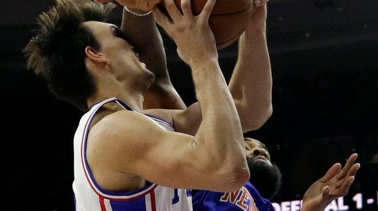 New York Knicks' Kyle O'Quinn, right, fouls Philadelphia