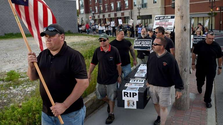 Protesters in Patchogue hold a mock funeral on