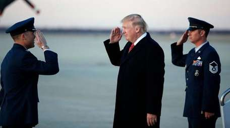 President Donald Trump salutes as he stands on