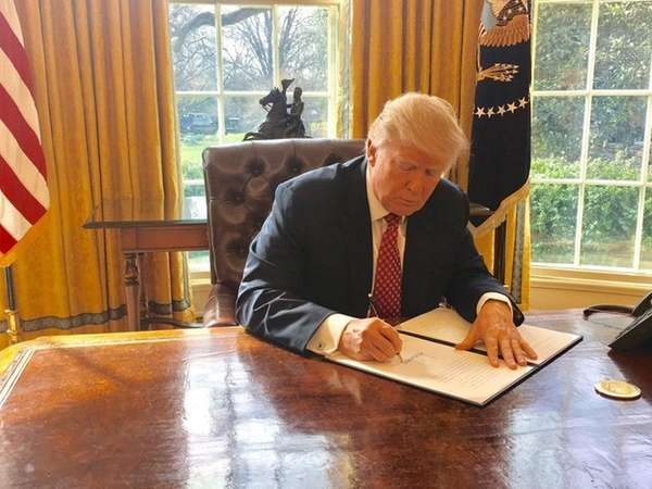 President Donald Trump signs a revised travel ban