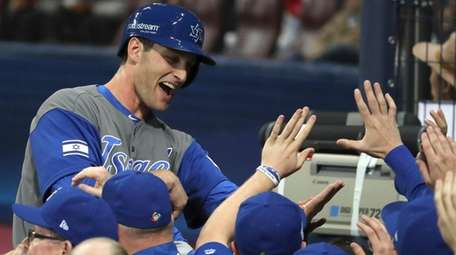 Israel's Nate Freiman celebrates with teammates after a