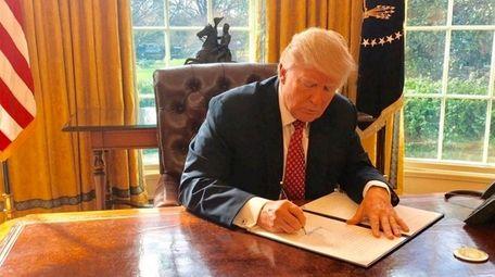 President Donald Trump signs a new executive order