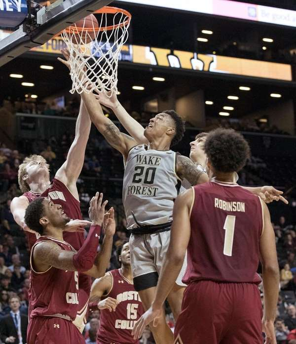 Wake Forest forward John Collins (20) goes to