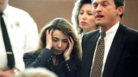 Amy Fisher, standing beside attorney Eric Naiburg, reacts