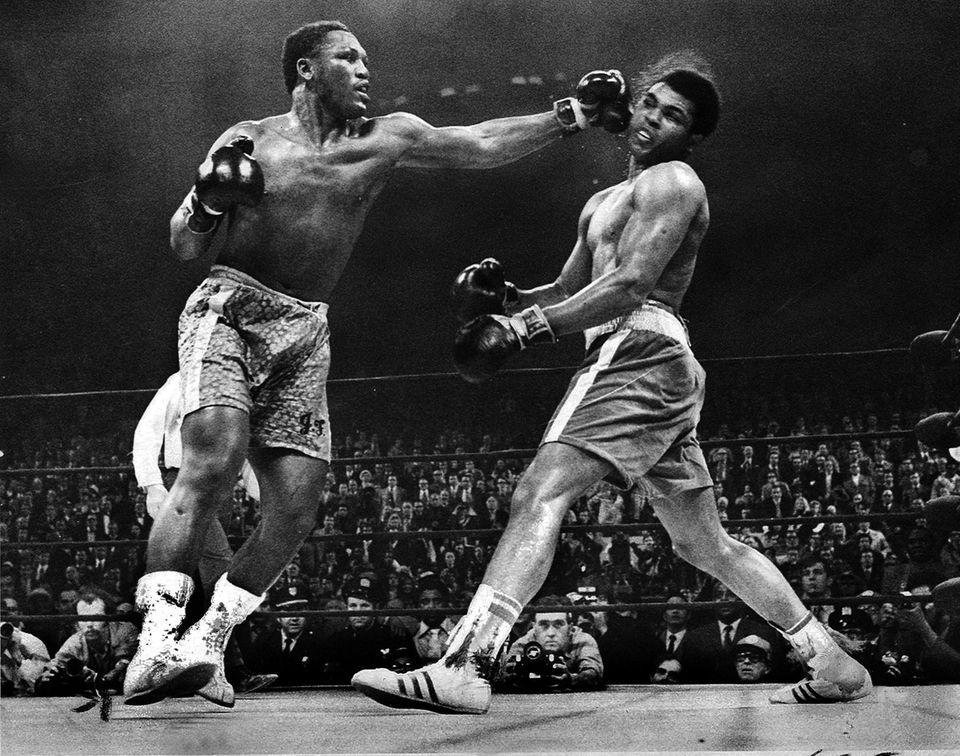 Joe Frazier, left, hits Muhammad Ali during the