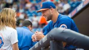 Tim Tebow signs a ball for Mackenzie Demers,