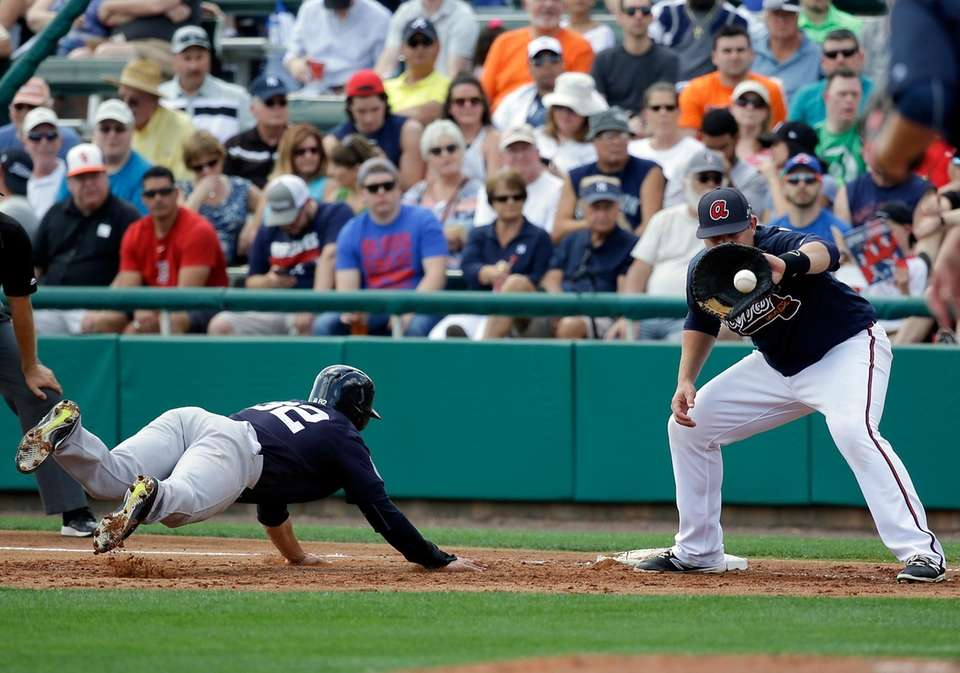 New York Yankees' Tyler Wade, left, dives back