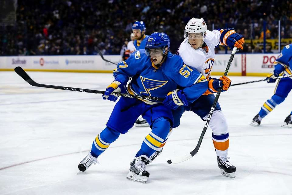 St. Louis Blues' David Perron, left, fights off