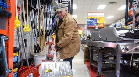 Steve Schnittger of Huntington looks at snow shovels