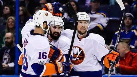 New York Islanders' Nick Leddy, center, is congratulated