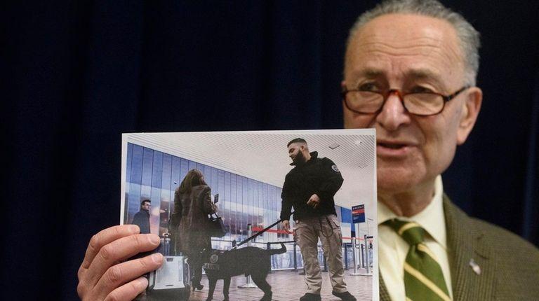 Sen. Chuck Schumer holds a photo of a
